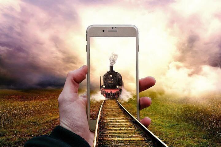 Eine Dampflokomotive in einem SmartPhone. Symbolisiert: Mit Volldampf ins Internet.