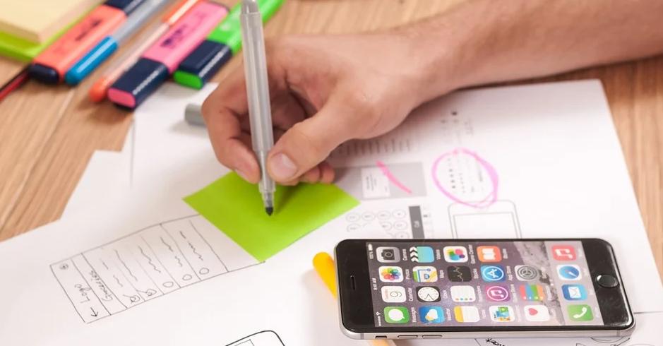 Eine schreiben Hand auf einem grünen Notizzettel (darunter weitere Blätter mit Planungsskizzen). Es liegt auch ein Smartphone auf dem Tisch.