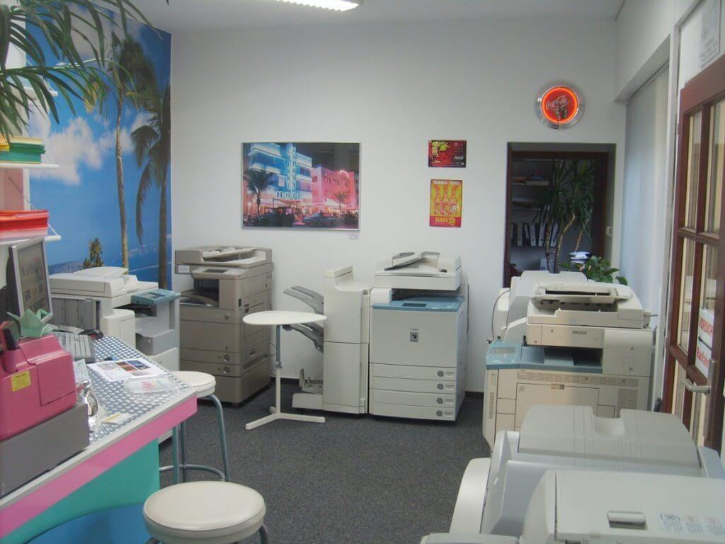 Unser CopyShop von innen. Es sind 5 Kopiergeräte abgebildet. Weitere Objekte: Die Kasse, Bilder an der Wand, Pflanzen, Barhocker etc.